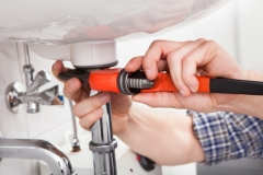 Young plumber fixing a sink in bathroom
